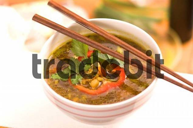 Product picture chinese soup with coriander and chopsticks Asian cooking